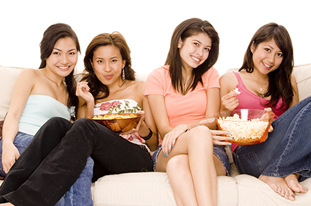 girls eating popcorn on a couch