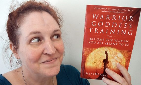 carma holds a copy of warror goddess training by heatherash amara
