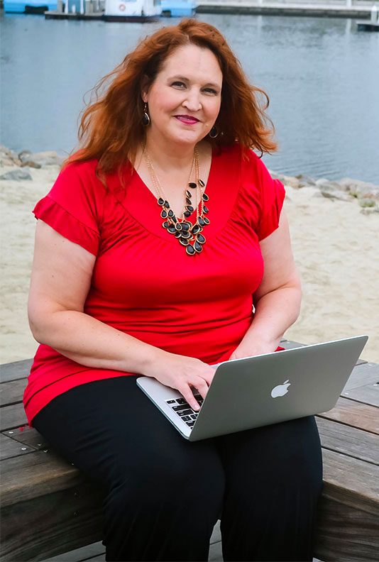 Carma at a computer by the water