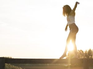a woman walking on a log, keeping balance